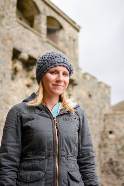 A young, blond woman in a beanie stands in front of Eilean Donan Castle