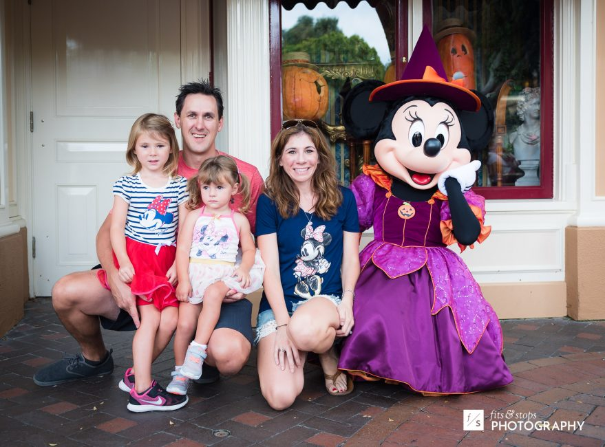 A young family poses with Minnie Mouse at DIsneyland.