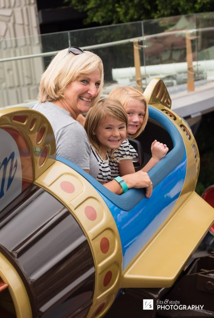 A photo of a grandmother and her granddaughters riding a rocket at Disneyland.