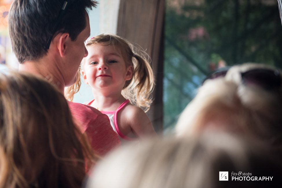 A young girl is held in her father's arms in front of a Disneyland ride.