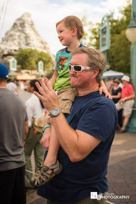 A young boy sits on his grandfather's shoulder during a parade at Disneyland.