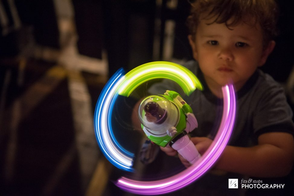A young boy holds a Buzz Lightyear toy surrounded by light trails.