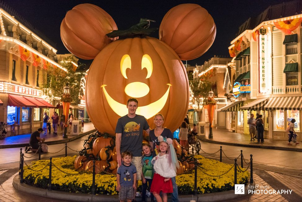 A family is photographed in front of a giant Mickey Mouse jack 'o latern at Disneyland.