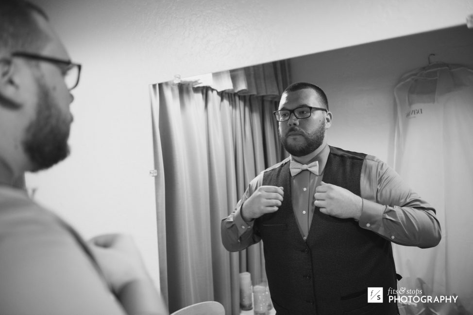 Black and white photo of a grrom getting dressed for his wedding ceremony.