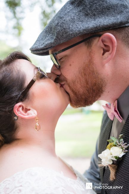Photograph of a young bride and groom kissing. The groom wears a driving cap.