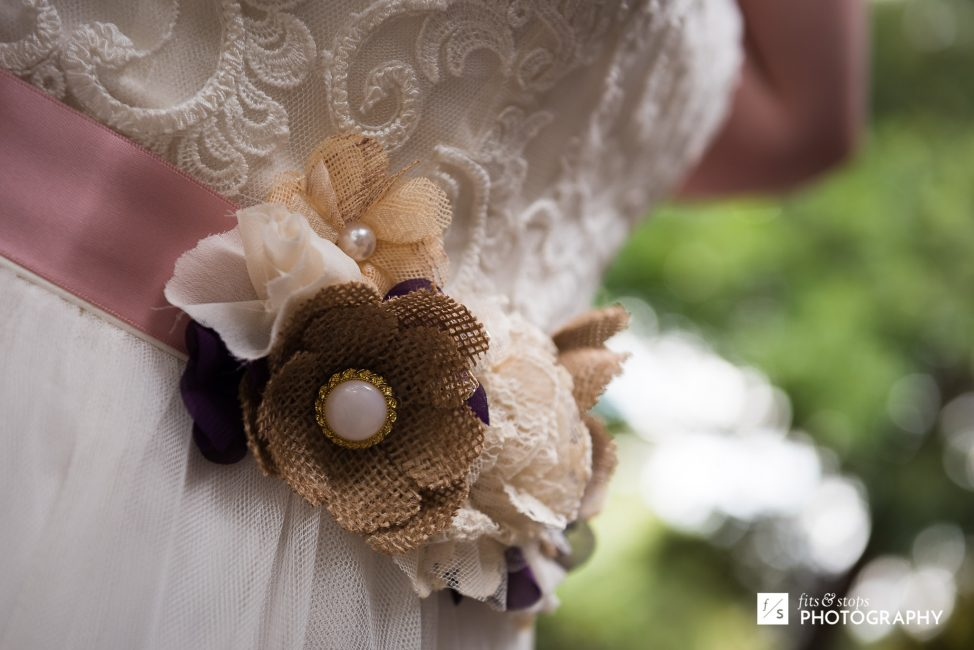 Close up photograph of a floral ornament on a young bride's wedding dress.