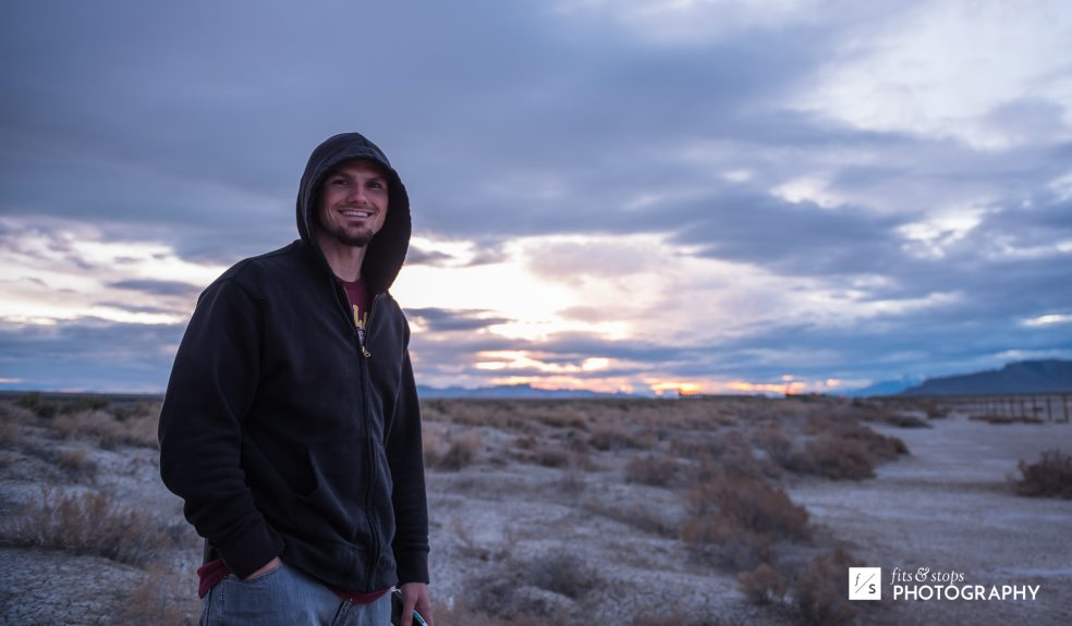 A photography of a young man in a hoodie walking across the Utah Salt Flats.