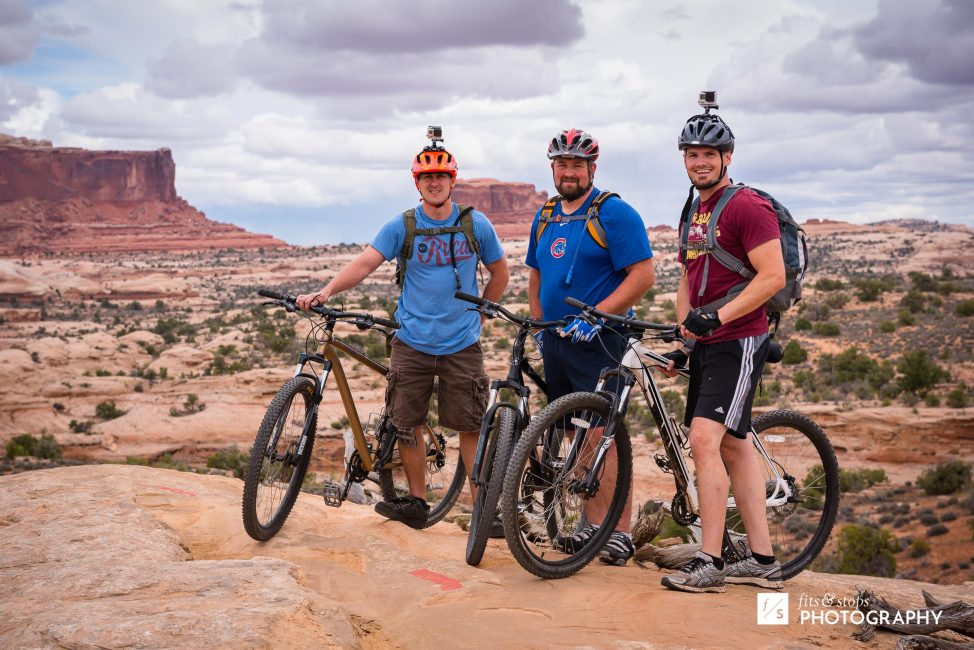 Photograph of three mountain bikers against the red mesas of Navajo Rocks trail in Moab, Utah.