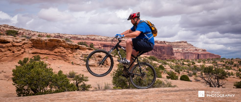 Photograph of a man pulling a wheelie on a mountain bike at Navajo Rocks trail in Utah.