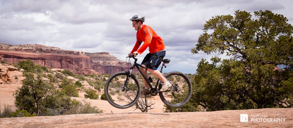 Photography of a young man jumping his mountain bike at Navajo Rocks trail in Utah.