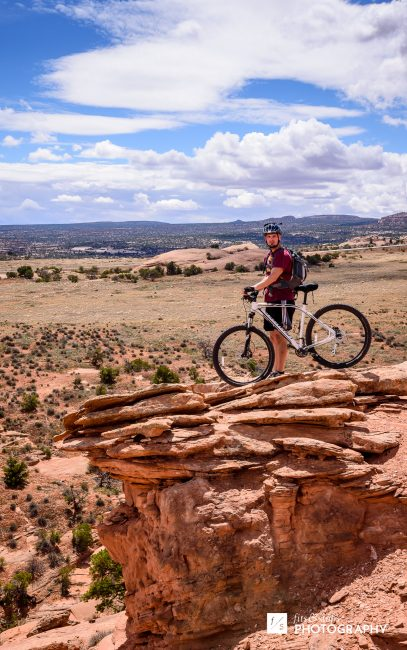 Photograph of a young man and a mountain bike, looking out over a precipice in Moab, Utah..
