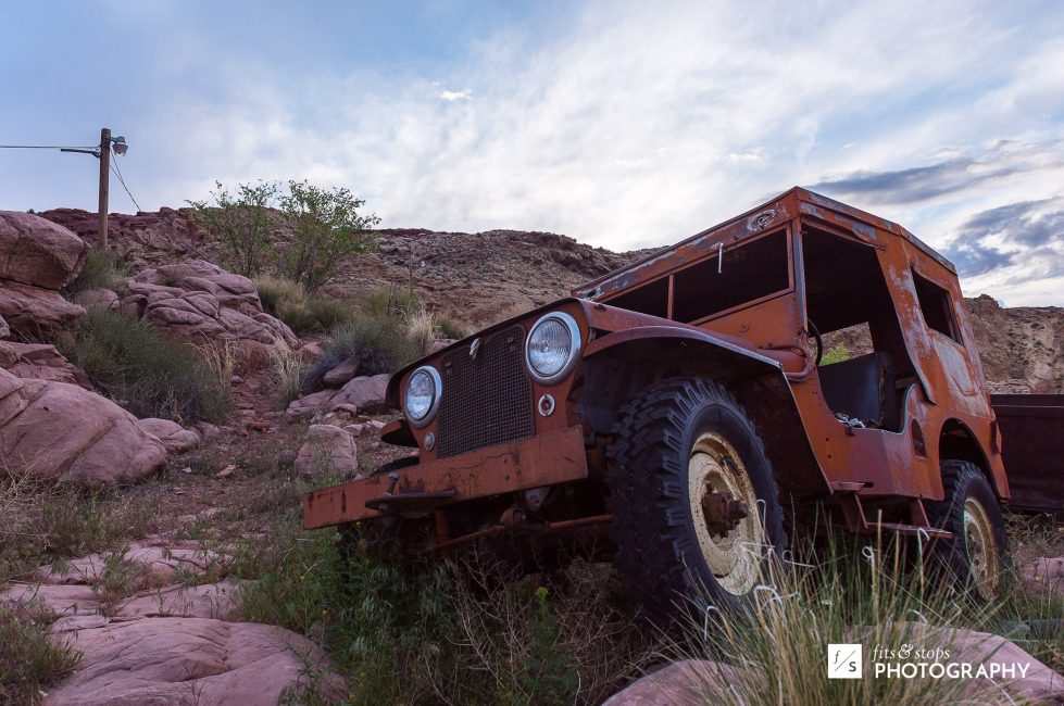 A photograph of a beat up old jeep along a Moab, Utah hillside.