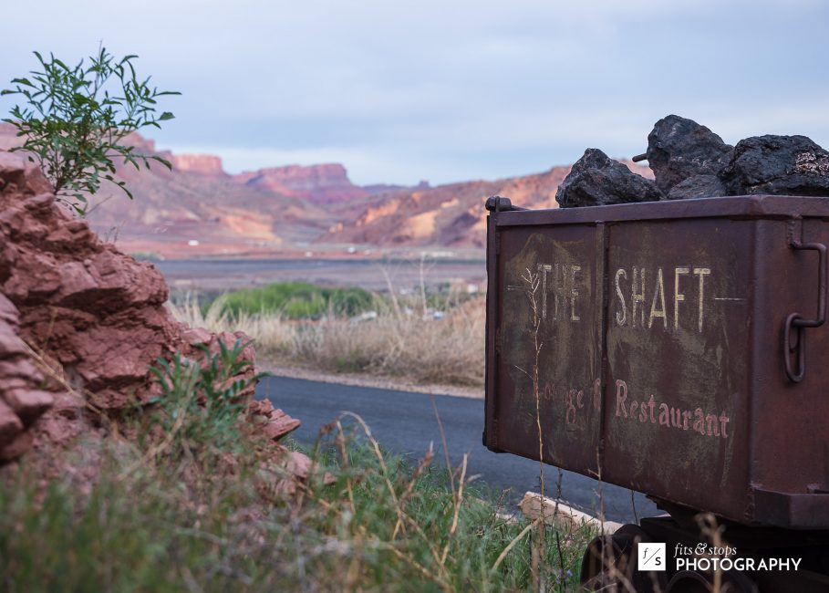 Photograph of an out of use minecart with the landscape of Moab, Utah in the background.