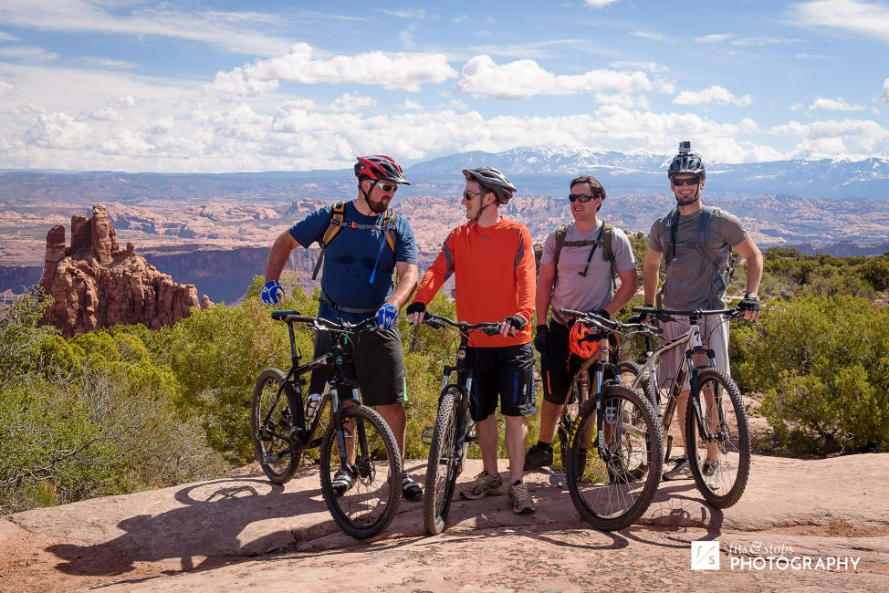 Four young men pose with their mountain bikes near a look out at Dead Horse Point State Park.