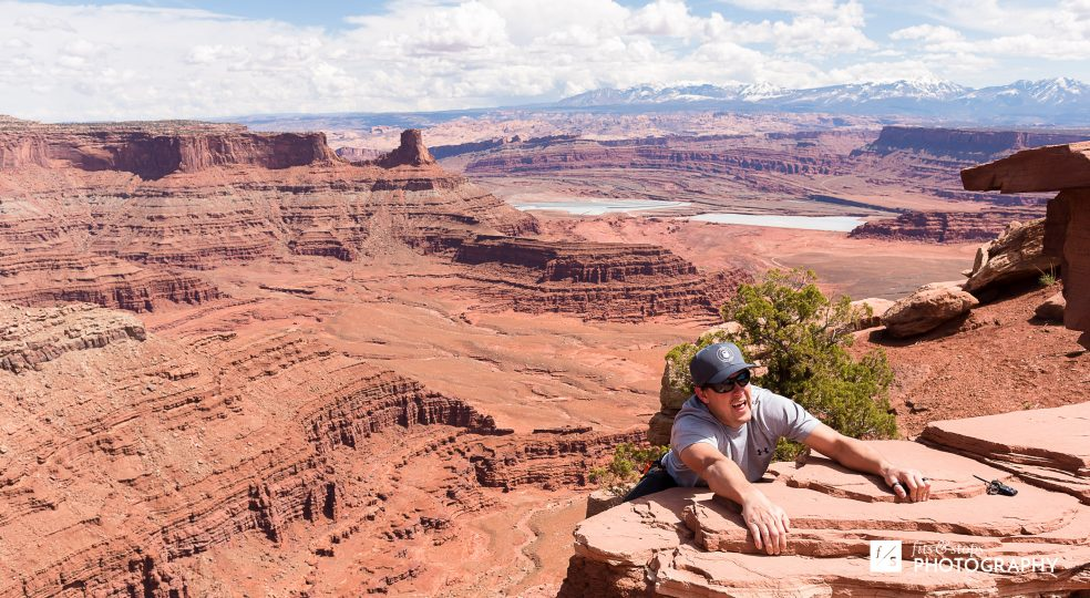 Photograph of a young man pretending to cling to the edge of a canyon ledge near Dead Horse Point State Park.