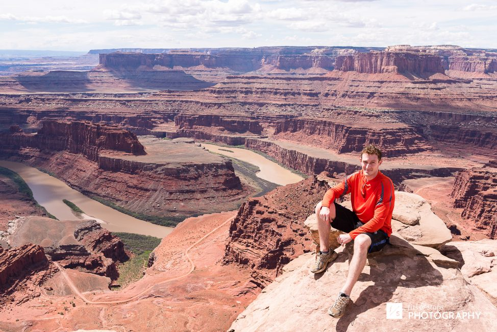Photograph of a young man on a cliff ledge overlooking Dead Horse Point near Moab, Utah.