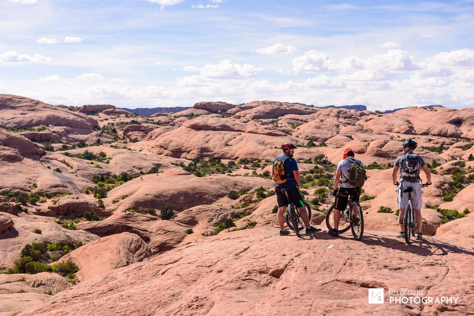 Three mountain bikers pause their ride to look out over the sandstone slopes of Slickrock trail near Moab, Utah.