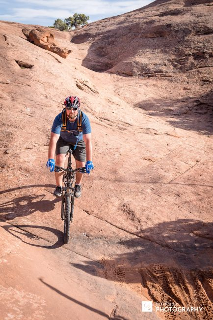 Photograph of a mountain biker riding downhill at Slickrock Trail near Moab, Utah.
