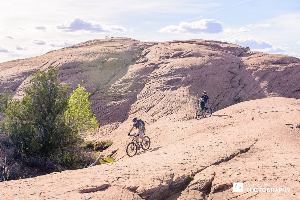 Photograph of two mountain bikers riding down the sandstone slopes of Slickrock Trail near Moab, Utah.