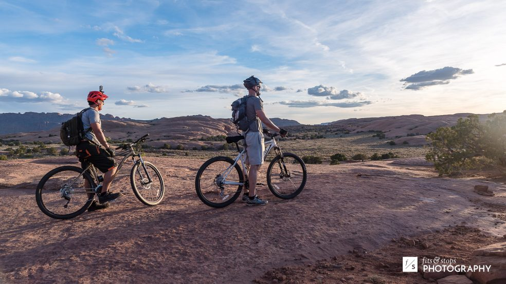 Photograph of two mountain bikers looking toward the sunset at Slickrock Trail, near Moab, Utah.
