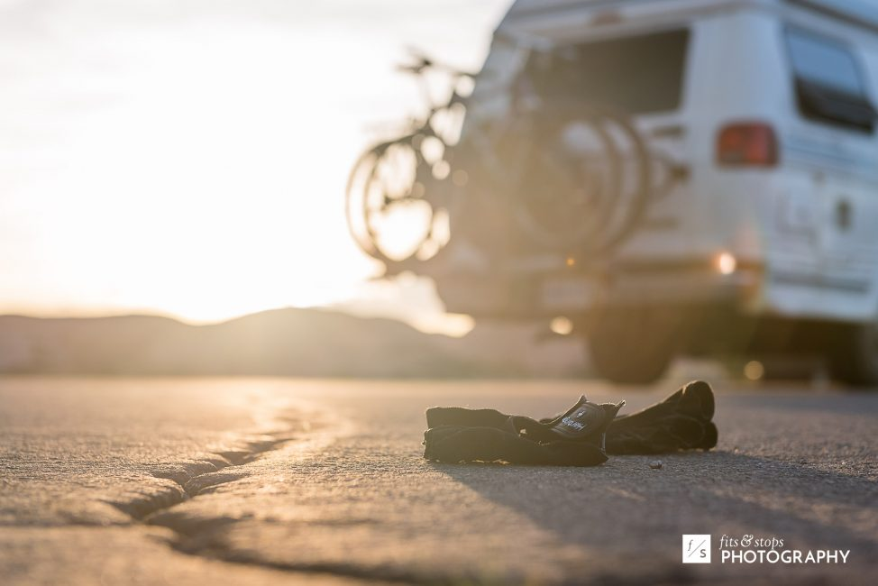 Shallow depth of field photograph of bike gloves on the asphalt at sunset near Slickrock Trail in Moab, Utah.