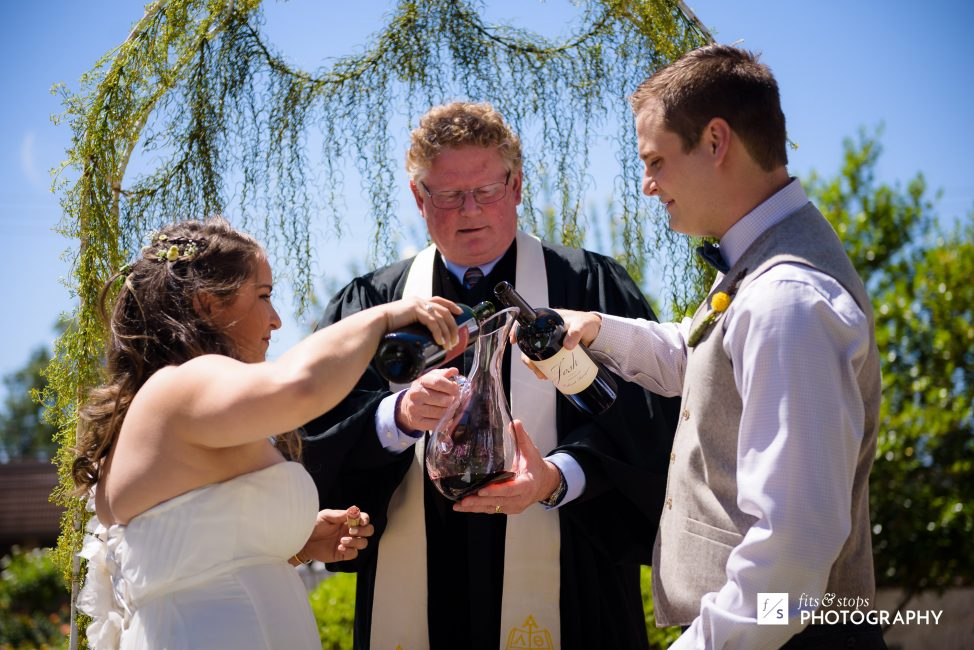 A photograph of a young bride and groom pouring wine from their own bottles into a single glass carafe.