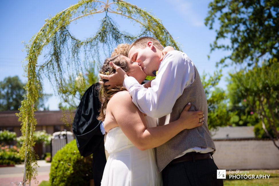 A photography of a young bride and groom kissing at the conclusion of their wedding ceremony.