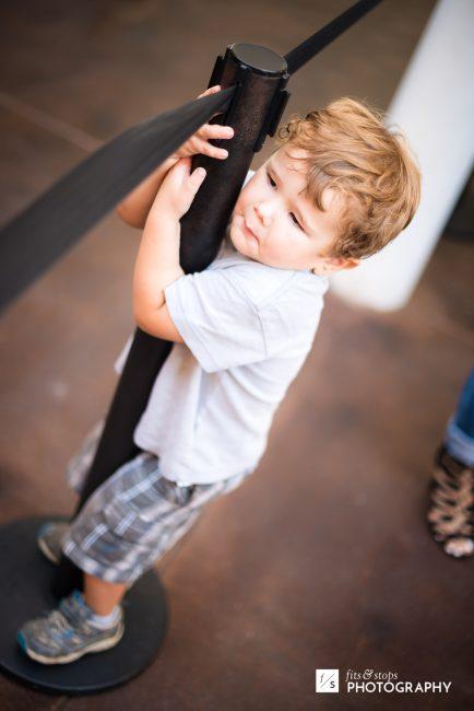 A little boy waits to enter an amusement park.