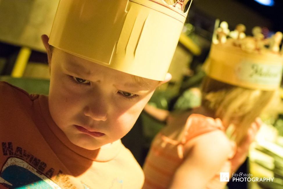 A young boy wearing a crown also wears a frown.