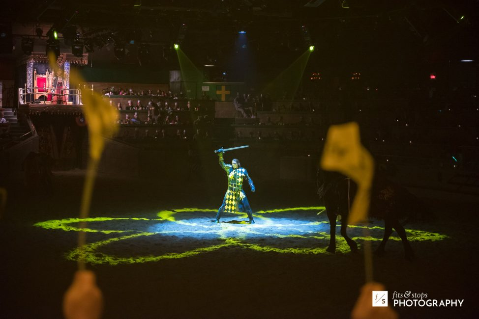 A knight dressed in yellow holds a sword aloft at Medieval Times Dinner Theater.