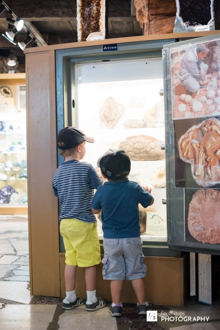 Two little boys in baseball caps look at a geode exhibit at Knott's Berry farm.