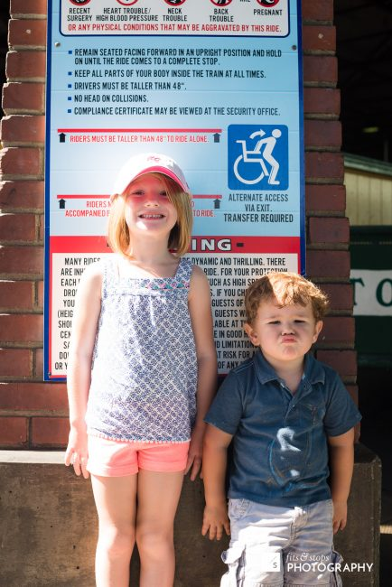 A young girl and boy measure up in front of a amusement park ride. One makes it, one doesn't.