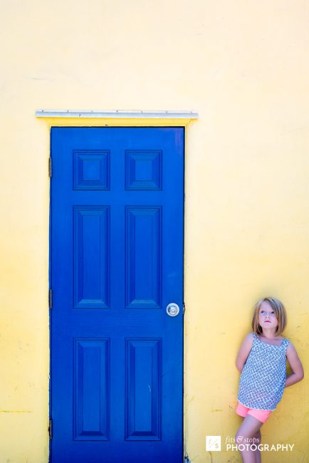 A young, blond girl leans against a yellow wall next to a blue door.