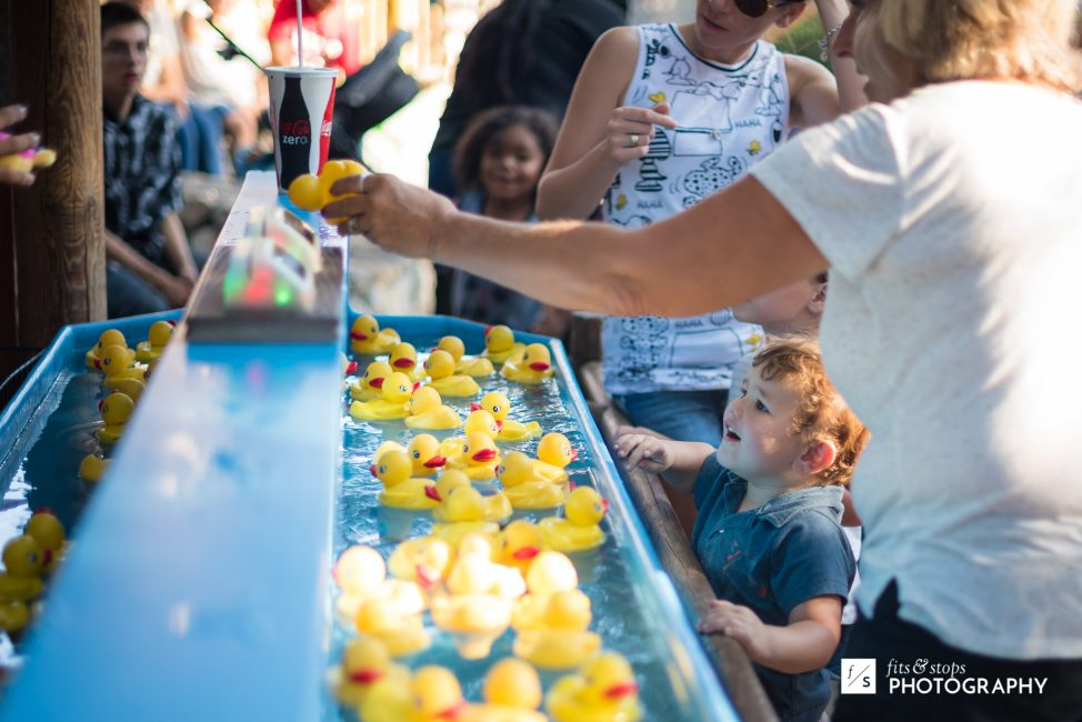 A young boy and his grandmother play with a procession of rubber duckies at Knott's Berry Farm.