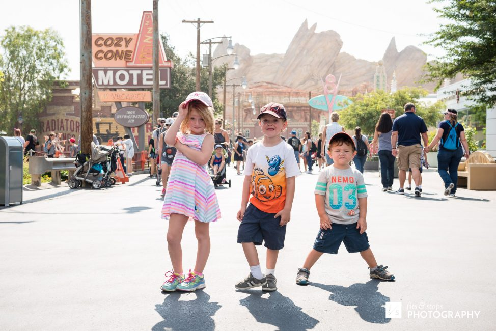 Three young kids standing in the main street of Radiator Springs.