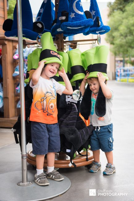 Two boys wearing goofy hats at a California Adventure shopping stall.