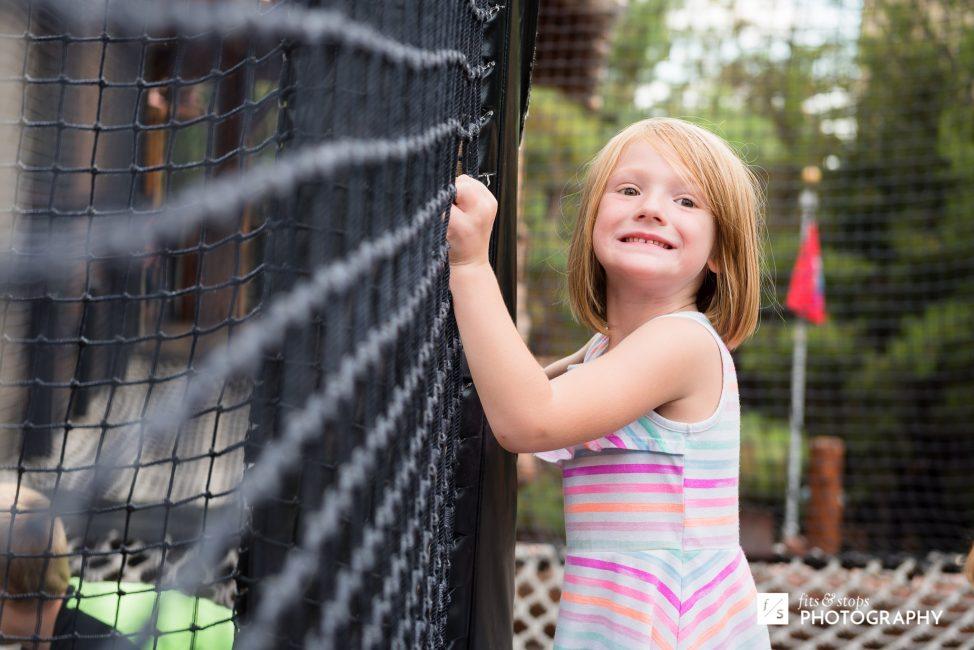 A young girl crosses a net bridge at California Adventure.