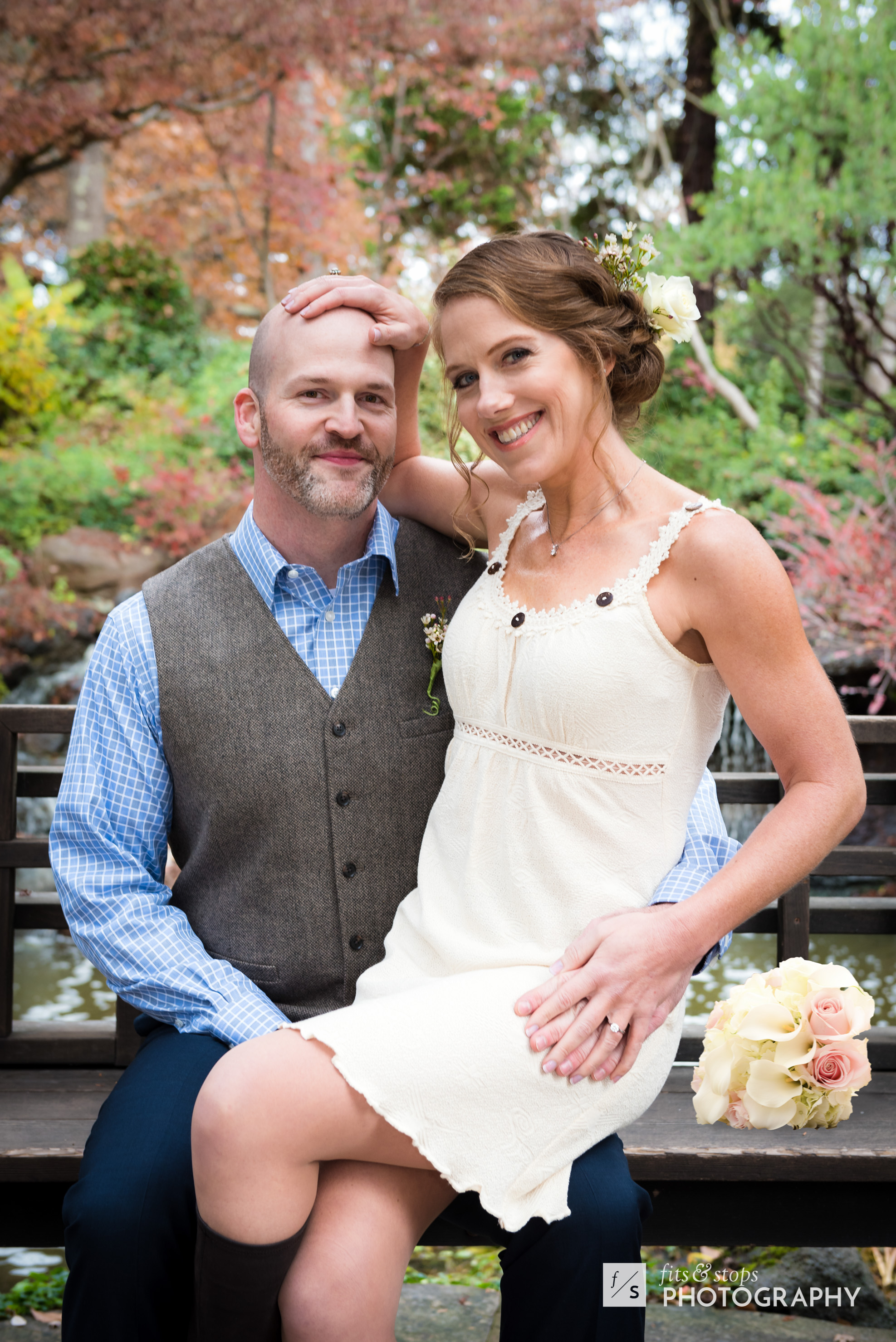 A newly married bride sits on her groom's lap, caressing his bald head with her hand.