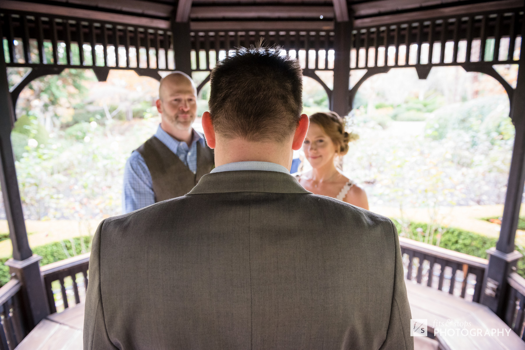 A pastor dressed in a sport coat officiates a wedding ceremony for a young, Caucasian bride and groom, set in a garden gazebo.