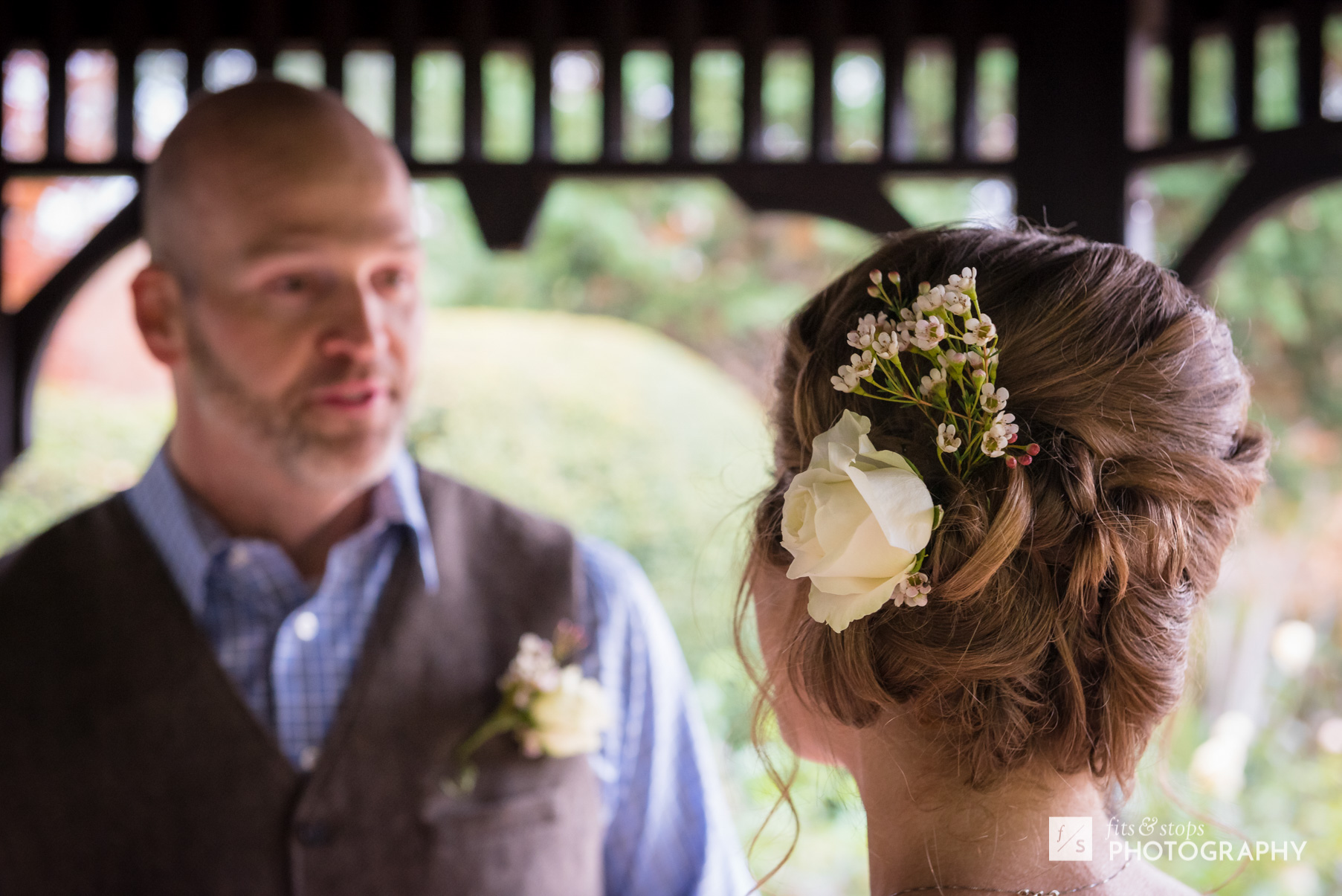 A Caucasian groom looks longingly at his bride during their wedding ceremony in a garden gazebo.