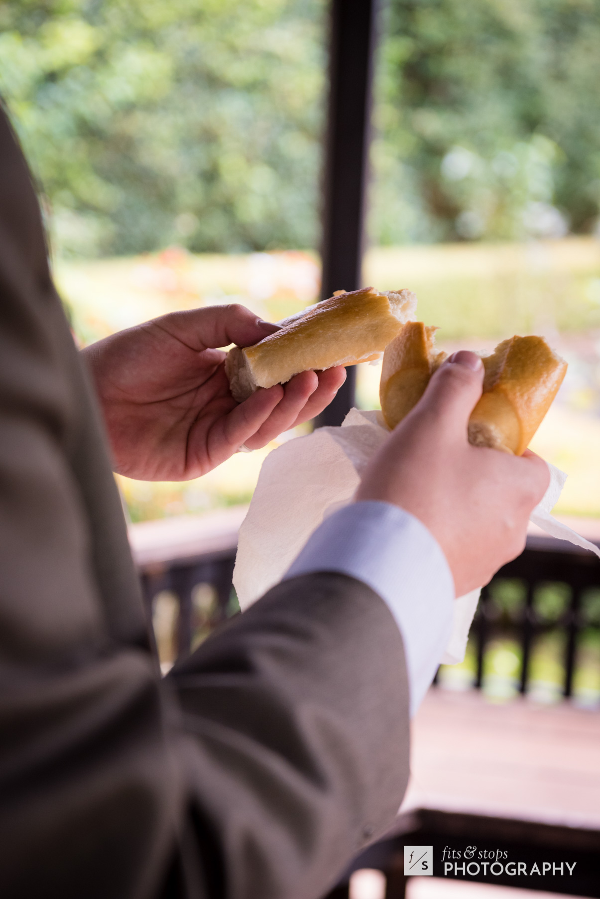 A pastor breaks a loaf of bread during a wedding ceremony, celebrating communion with the bride and groom.