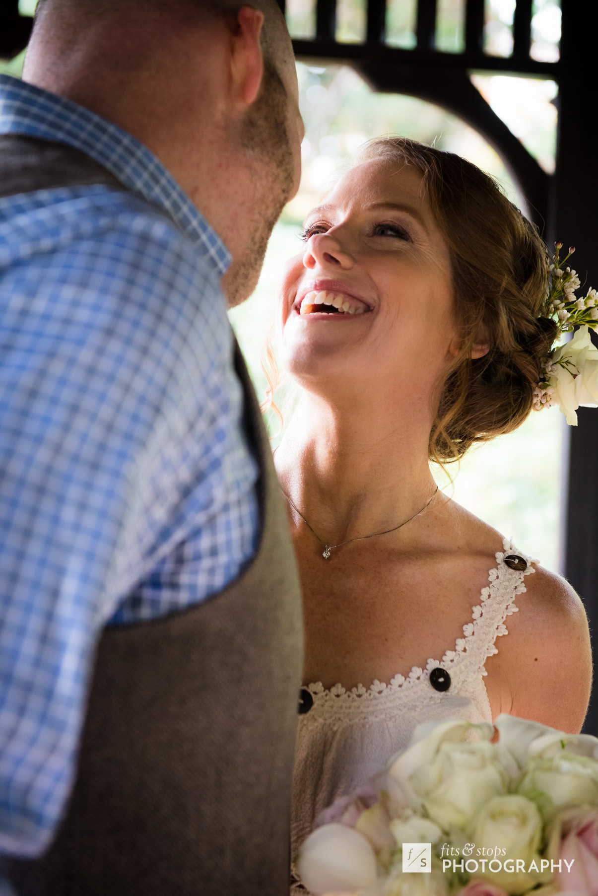 A young bride looks up at the face of her groom during a wedding ceremony underneath a gazebo,