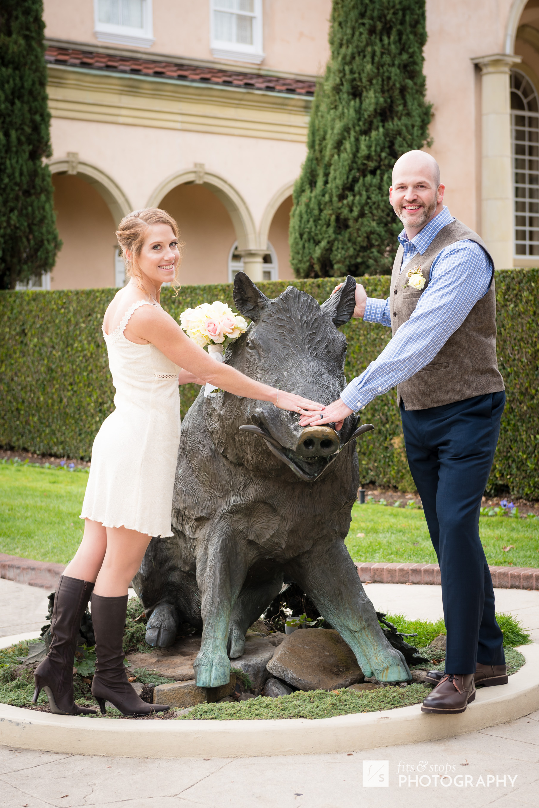 """A newly married bride and groom stroke the snout of a """"boardeaux"""", a bronze statue immortalized at the Ferrari-Carrano Winery."""