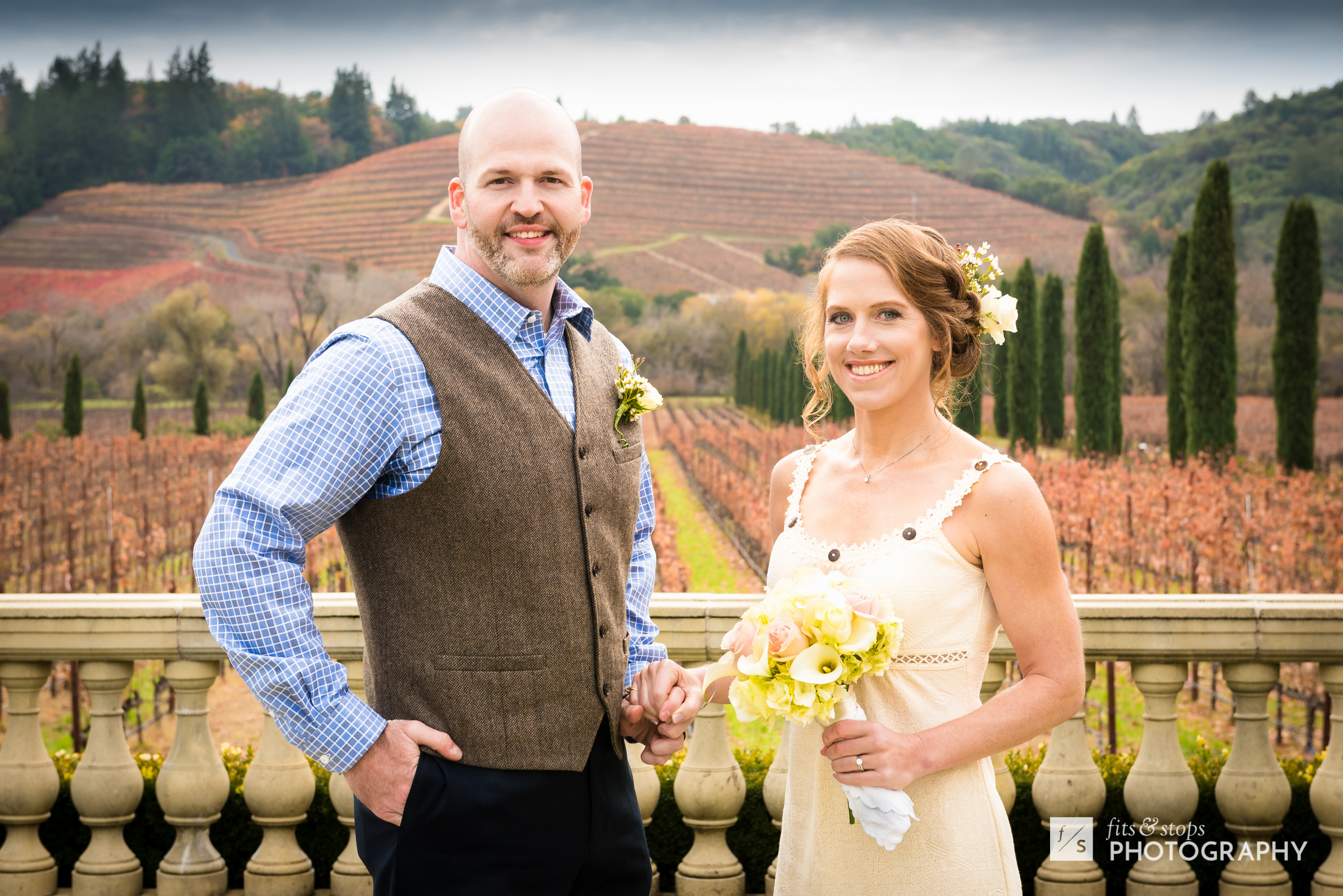 A newly married couple poses for a photograph in front of a vineyard in Northern California.