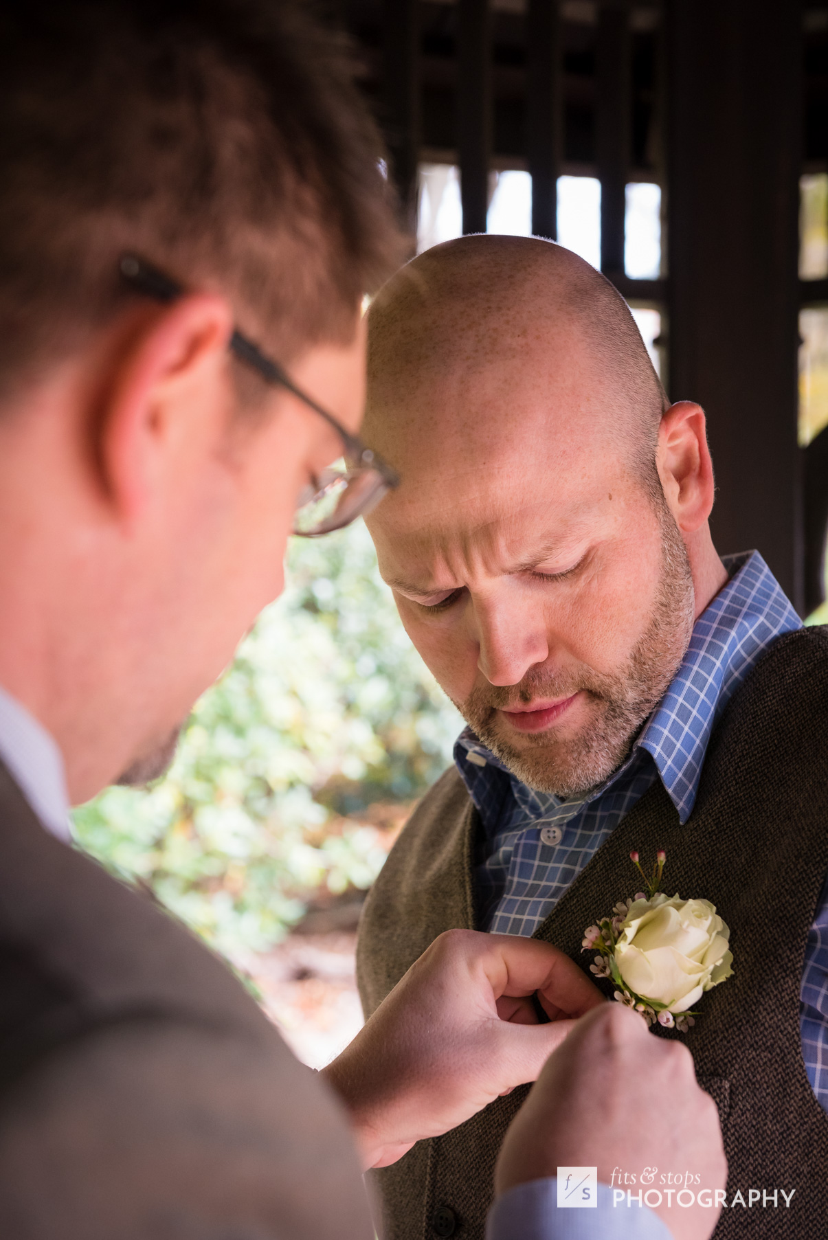 A young groom allows his friend to pin a boutonniere on his chest.
