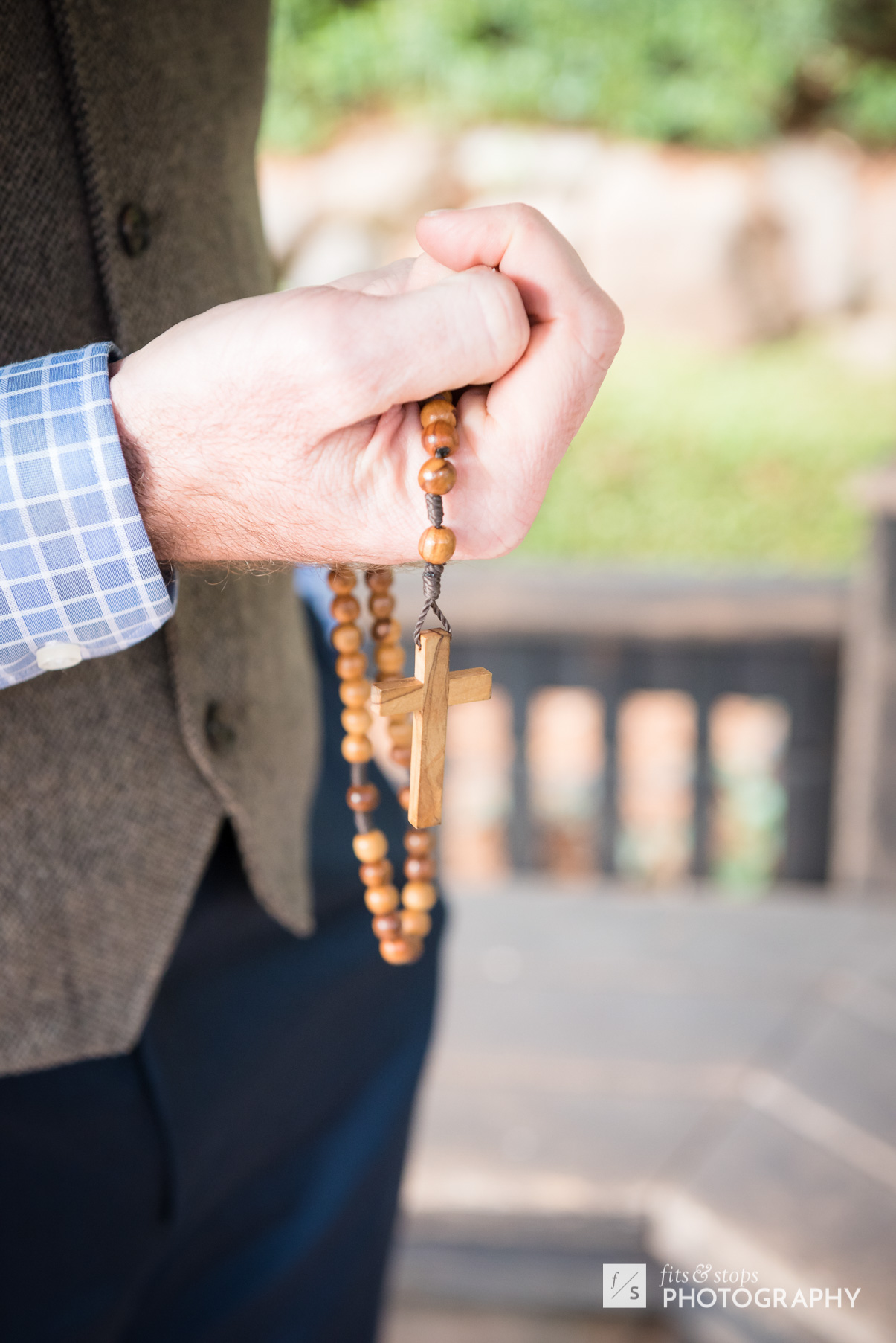 A young groom holds a keepsake wooden cross necklace in his hand
