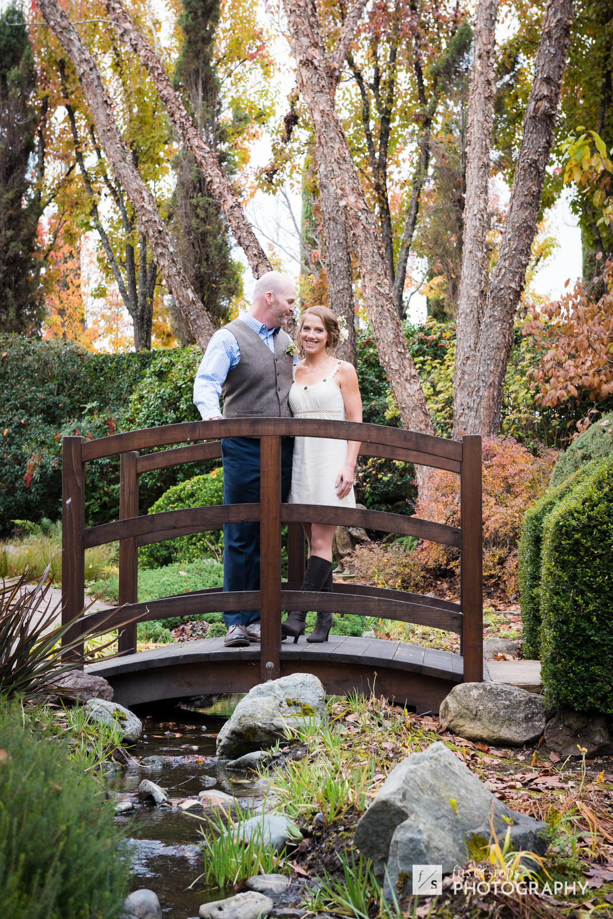 A newly married caucasian couple embraces following their wedding ceremony in a garden, standing on a bridge.
