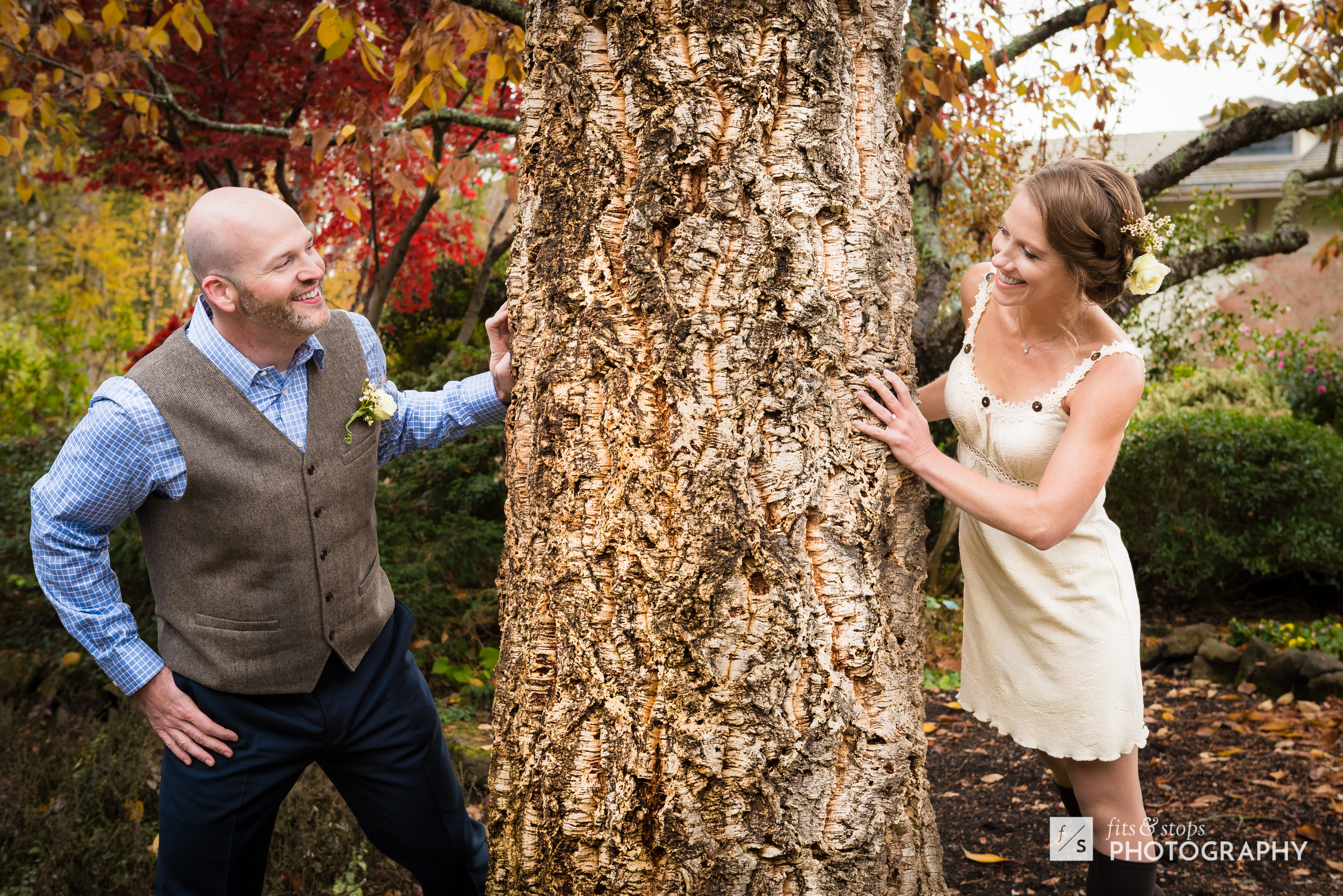 A newly married couple plays a game of hide and seek around a towering tree in a lush garden.