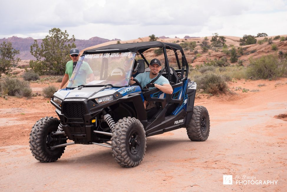Photography of young men sit inside a razor four-wheeler in a desert course near Moab, Utah.