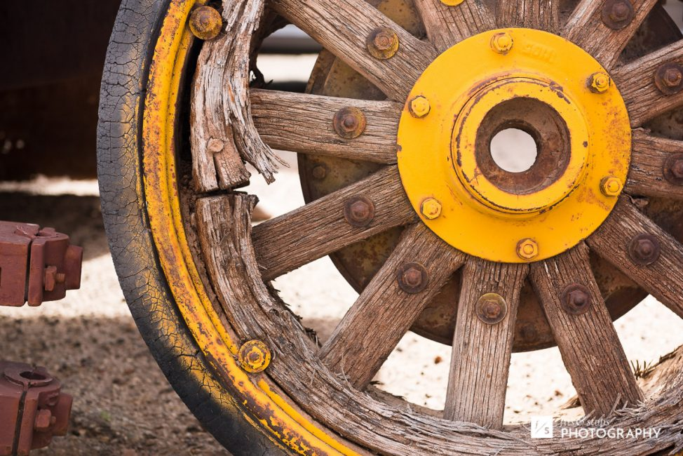 Close up photograph of a weathered old wagon wheel in the Utah desert.